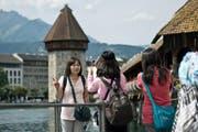 Touristen fotografieren sich vor der Kapellbrücke in Luzern. (Bild Pius Amrein)