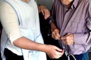 Eine Mitarbeiterin der Spitex hilft einem betagten Mann. Themenbild. (Bild: Nadia Schärli / Neue Luzerner Zeitung)
