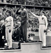 Siegerehrung im Weitsprung: Jesse Owens (Mitte) salutiert, Luz Long (rechts) zeigt den Hitlergruss. (Bild: Keystone)