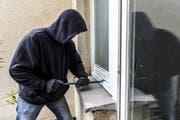 Ein Einbrecher versucht in eine Wohnung einzudringen (gestellte Szene). (Bild: Imago)