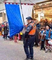 Beim Kinderumzug am Güdisdienstag in der Stadt Luzern springt ein Polizist als Fahnenträger ein. (Bild: Leserbild Walter Linke)
