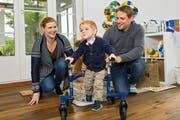 Timo (mit seinen Eltern Petra und Björn Portmann) hat in den letzten Monaten viel erreicht. Das Gehen am Minirollator ist eine seiner neuen Fähigkeiten. (Bild: Eveline Beerkircher/LZ)
