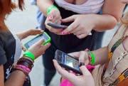 So gut wie jeder besitzt ein Handy oder Smartphone - über die nötigen Mobilfunkantennen wird aber heftig diskutiert. (Bild: Keystone/Martin Rütschi)