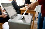 Ein Mann wirft ein Couvert in eine Abstimmungsurne. (Bild: Keystone)