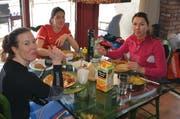 Erst die Arbeit, dann der Genuss: Michelle Gisin (links), Physiotherapeutin Miryam Leyrer (Mitte) und Wendy Holdener beim Mittagessen, das sie selbst gekocht haben. (Bild: Stefan Klinger)