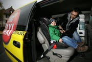 Taxifahrer Daniel Krummenacher von Mc Taxi Luzern montiert den Kindersitz seines Sohnes Rian (3 Jahre) in seinem Taxi. (Bild Chris Iseli/Neue LZ)