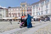 Nora Illi (im grünen Niqab), Frauenbeauftragte des Islamischen Zentralrats der Schweiz, am 1. Juli 2016 auf der Piazza Grande in Locarno. Mit diesem Auftritt provozierte sie die erste Busse aufgrund des Burka-Verbots. (Bild: Keystone/Paplo Gianinazzi)