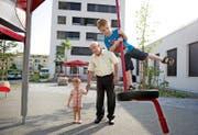 Jost Schumacher mit Lukas (4), der sich auf den Kindergarten freut, und dessen Bruder Dominik (1) vor dem Kindergarten Tribschenstadt 2 (Erdgeschoss, weisses Gebäude hinten). (Bild Corinne Glanzmann)