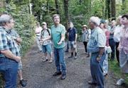 Thomas Neurauter, Vorstandsmitglied von Pro Natura Zug, führt eine Gruppe durch den Wald. (Bild: Werner Schelbert (Hagendorn, 22. Juli 2017))
