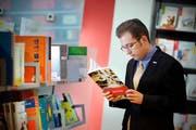 Alain O. Probst, Präsident der Jungfreisinnigen Amt Sursee, beim Durchblättern eines der betreffenden Lehrmittel in einer Buchhandlung. (Bild Pius Amrein/Neue LZ)
