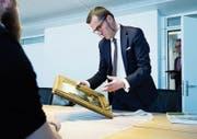 Experte Stefan Puttaert von Sotheby's Zürich nimmt ein Gemälde aus dem 18. Jahrhundert unter die Lupe. Rund 70 Zugerinnen und Zuger haben am gestrigen Expertentag ihre Preziosen zur Begutachtung vorbeigebracht. (Bild: Stefan Kaiser (Zug, 4. April 2017))