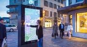Eine Frau bedient die digitale Stadtkarte am Schwanenplatz. (Bild: Clear Channel / Kilian J. Kessler)