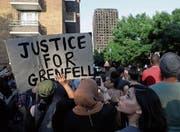 «Gerechtigkeit für Grenfell»: Demonstranten vor dem abgebrannten Hochhaus im Stadtbezirk Kensington. (Bild: Tim Ireland/AP (London, 16. Juni 2017))