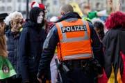 Ein Polizist kontrolliert einen Fasnächtler am Schmutzigen Donnestag in Luzern. (Bild: Alexandra Wey (Luzern, 24. Februar 2017))