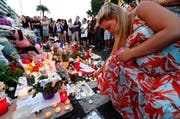 Personen legen in Nizza Blumen nieder. (Bild: AP / François Mori)