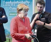 Bundeskanzlerin Angela Merkel lässt sich von Martin Rabl von Giants Software das Videospiel «Landwirtschaftssimulator» auf der Playstation 4 erklären. (Bild: Martin Meissner/Keystone (Köln, 22. August 2017))