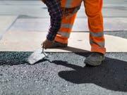 Ein Bauarbeiter beim Bodenlegen (Archiv) (Bild: Keystone)