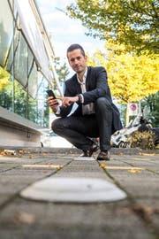 Oliver Stahel auf einem Parkplatz mit Sensor. Dieser meldet ans Smartphone, wenn der Platz frei ist.