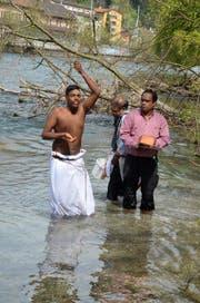 Der Sohn des Verstorbenen (links) bespritzt sich mit Wasser, nachdem er die Asche seines Vaters der Reuss übergeben hat. (Bild Benno Bühlmann)