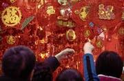 In Peking gibt es bereits zahlreiche Dekorationen zur Feier des Hundejahres zu sehen. (Bild: Mark Schiefelbein/AP (13. Februar 2018))