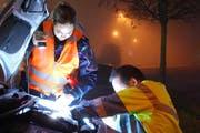 Eine Polizistin leuchtet das Arbeitsfeld eines TCS-Servicemanns aus. (Bild: Luzerner Polizei)