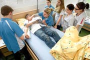 Ein angehender Fachmann Gesundheit (links) entnimmt unter Instruktionen der Ausbildnerin und unter den Augen seiner Kolleginnen eine Blutprobe. (Bild Nadia Schärli)
