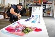 Lars Fricker von Fuchs-Design AG begutachtet ein Dominique-Gisin-Plakat. (Bild: Corinne Glanzmann / Neue OZ)