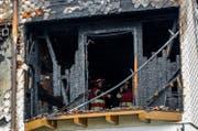 Einsatzkräfte im komplett niedergebrannten Zweifamilienhaus. (Bild: Philipp Schmidli (Schachen, 11. Februar 2018))