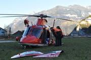 Zwei Polizeibeamte inspizieren den beschädigten Rega-Helikopter. Für die Rettung der Verunfallten wurden die Türen des Helikopters entfernt. (Bild: Anian Heierli / Neue UZ)