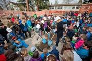 Stadträtin Manuela Jost und Volksschulrektor Rolf von Rohr (Mitte, leicht verdeckt) mit Felsberg-Schülern beim Vergraben der Schatztruhe mit guten Wünschen für die Schulhaussanierung. (Bild: Dominik Wunderli / Neue LZ)