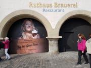 Werbeplakat von einer Dame mit Bierschaumschnauz vor dem Restaurant Rathaus Brauerei (Bild: Ramona Geiger)