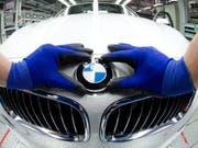 Ein Angestellter bringt bei einem BMW das Marken-Logo an (Archiv) (Bild: Keystone)