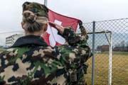 Eine Frau in der Schweizer Armee: Morgens beim Antrittsverlesen wird die Schweizer Flagge gehisst, in Achtungstellug gestanden und die Fahne gegrüsst. Aufgenommen wurde das Bild während der Ausbildung zu Swisscoy Soldaten, in der Nähe der Kaserne in Stans im Jahr 2014. (Bild: Keystone)