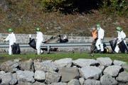 Spezialisten der Schweizer Armee und Polizeiforensiker untersuchen den Unfall nach dem Absturz eines F/A-18 am 24. Oktober 2013 bei Alpnach. (Bild: Keystone / Urs Flüeler)
