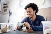 «Man kann aus Papier fast alles machen»: Sipho Mabona mit selbst entworfenen Origami-Tieren - Stier, Trilobit (ein Gliederfüssler) und Tintenfisch. (Bild: Manuela Jans / Neue LZ)