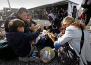 Eine Flüchtlingsfamilie bei der Rast in der Nähe von Tabanovce, Mazedonien. Vom dortigen Transitcenter geht ihre Reise weiter über die serbische Grenze nach Presevo. (Bild: Keystone/Boris Grdanoski)