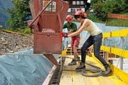 Reporterin Julia Stephan nimmt mit Polier Martin Odermatt auf einer Baustelle in Engelberg den Kübel mit Flüssigbeton in Empfang. (Bild: Dominik Wunderli / Neue LZ)