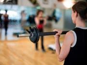 Eine Frau trainiert in einem Fitnessstudio (Archiv) (Bild: KEYSTONE)