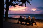 Männer verschiedenen Alters geniessen einen Sonnenaufgang am Bodensee in Rorschach. (Bild: Gian Ehrenzeller/Keystone)