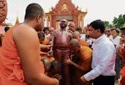 Buddhistische Mönche tragen eine Statue des prominenten Journalisten Kem Ley, der 2016 ermordet wurde. (Bild: Satoshi Takahashi/Getty (Phnom Penh, 14. Oktober 2016))