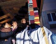 Die beiden Projektverantwortlichen Sandra Zgraggen (links) und Matthia Diener (rechts) enthüllen gemeinsam mit Vereinspräsidentin Yvonne Stadelmann das Strick-Kunstwerk an den Säulen des Vereinshauses. (Bild: Werner Schelbert (Menzingen, 22. Februar 2018))