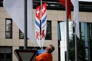 Mit Fahnen diesen Typs wird sich Cham in Zukunft beflaggen: Das Schweizer, Zuger und Chamer Wappen auf einem Tuch. (Bild: Stefan Kaiser / Neue ZZ)