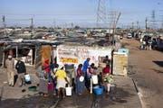 Bewohner der Langa Township in der Nähe von Kapstadt holen Wasser bei einer Sammelstelle. (Bild: MARTIN RUETSCHI (KEYSTONE))