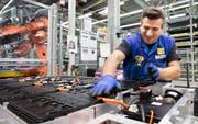 Der deutsche Automobilsektor braucht weniger temporäre Arbeitskräfte. Das Bild zeigt einen Festangestellten bei BMW. Bild: Matthias Schrader/AP (Dingolfing, 20. Januar 2015)