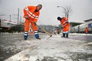 Mitarbeiter des Strasseninspektorats Luzern pickeln Eis auf den Parkplätzen beim Verkehrshaus Luzern. (Bild Manuela Jans/Neue LZ)