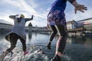 Zwei Schwimmerinnen beim Silvesterschwimmen springen in das kühle Nass der Reuss. (Bild: KEYSTONE/Urs Flüeler)