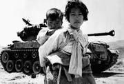 Mit ihrem Bruder auf dem Rücken stapft eine koreanische Jugendliche an einem Panzer der US-Armee vorbei. (Bild: R.V. Spencer/Keystone (Haengju, 9. Juni 1951))