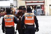 Zwei Polizisten unterhalten sich in Luzern mit einem Fasnächtler. (Bild: Jakob Ineichen (Luzern, 12. Februar 2018))