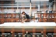 Ein Angestellter von Argolite arbeitet an einer neu installierten Anlage für Laminatplatten. Bild: Manuela Jans-Koch (Willisau, 11. November 2016)