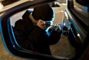 Ein Mann versucht in ein Auto einzubrechen (gestellte Szene). (Bild: Keystone)